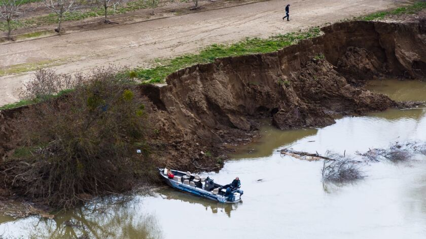 Residents inspect the eroded banks of the Feather River after state officials dramatically reduced the flow of water at the end of February.
