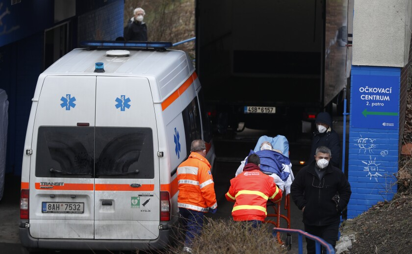 """Healthcare workers move a patient to the infectious ward of the Bulovka hospital in Prague, Czech Republic, Wednesday, Feb. 24, 2021. The Czech prime minister Andrej Babis said the pandemic situation in one of the hardest-hit country in the European Union, is """"extremely serious"""" and his government will have to impose more restrictive measures to slow down the spread of the coronavirus. (AP Photo/Petr David Josek)"""