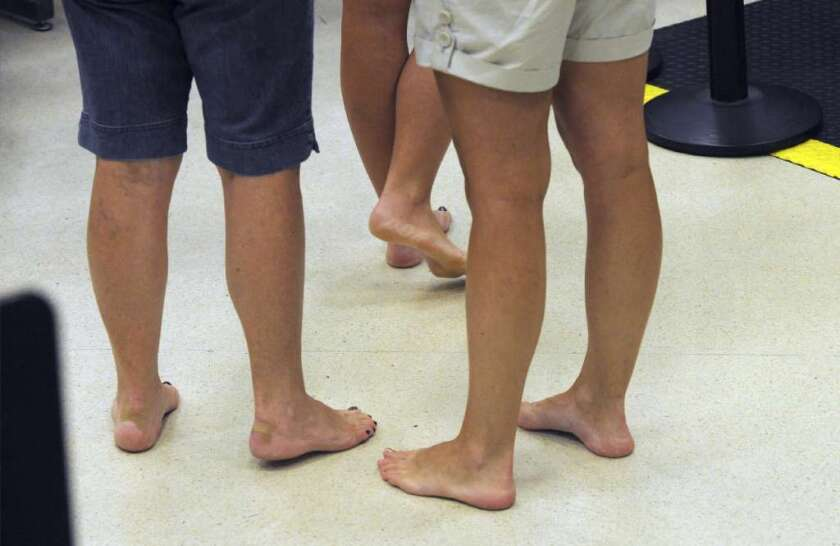 Barefoot passengers wait to retrieve their shoes while going through the Transportation Security Administration security checkpoint at Hartsfield-Jackson Atlanta International Airport.