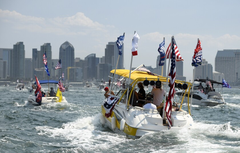 Boats fly flags as they take part in the boat parade for President Trump on the San Diego Bay.