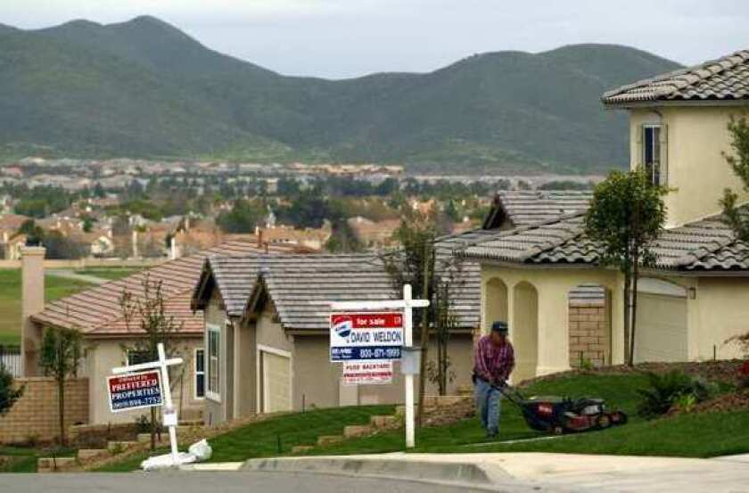 A man mows the lawn in front of homes with for sale signs out front
