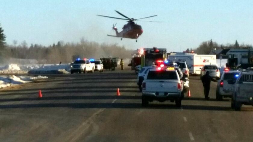 Emergency crews respond to the scene where a bus carrying a junior hockey team was struck by a truck in western Canada on April 6.