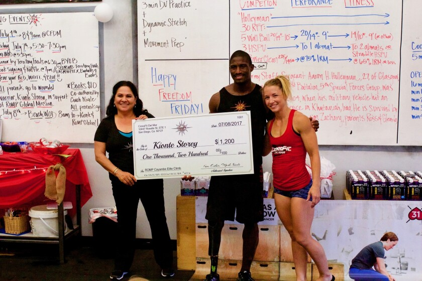 Kionte Storey with Esther Marek and Nicole Zapoli, co-owners of CrossFit Del Mar. The gym donated $1,200 for Storey's quest to raise funds for prosthetics for underprivileged amputees.