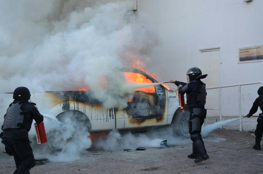 Riot police use extinguishers to put out the flames of a burning pick-up truck after it was set on fire in Chilpancingo, capital of Guerrero State, Mexico, Sunday, June 7, 2015. Next to the truck several molotov bombs were found. The incident comes on the day of the mid-term elections as a loose co