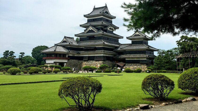 "Even from across the lawn, Matsumoto Castle, nicknamed ""Black Crow Castle,"" is impressive. A volunte"