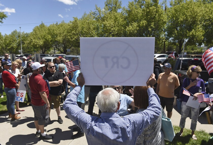 A man holds up a sign against Critical Race Theory during a protest