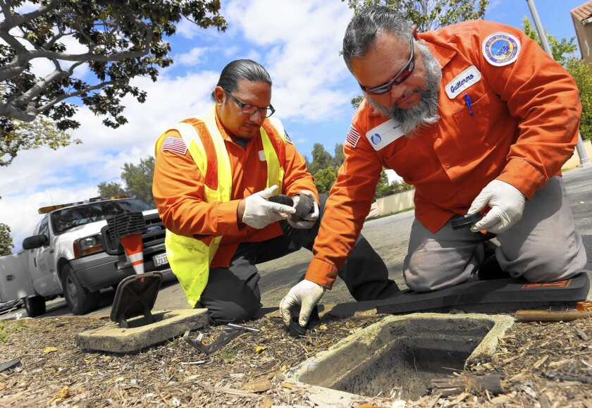 """City of Long Beach workers Jared Mataalii, left, and Guillermo Lopez remove a water meter in order to install a """"smart meter."""""""