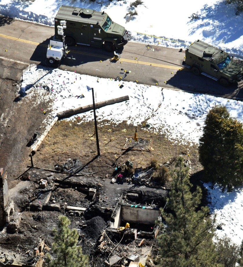 In this Feb. 13, 2013, aerial file photo, law enforcement authorities investigate the burnt-out cabin where quadruple-murder suspect Christopher Dorner died after barricading himself inside during a standoff with police in the Angeles Oaks area of Big Bear.