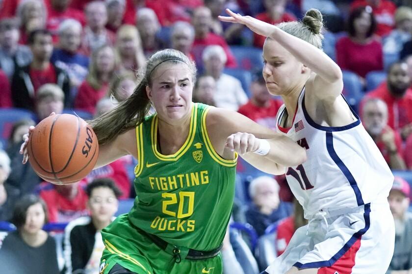 Oregon guard Sabrina Ionescu (20) drives around Arizona guard Mara Mote during the first half of an NCAA college basketball game Sunday, Jan. 12, 2020, in Tucson, Ariz. (AP Photo/Rick Scuteri)