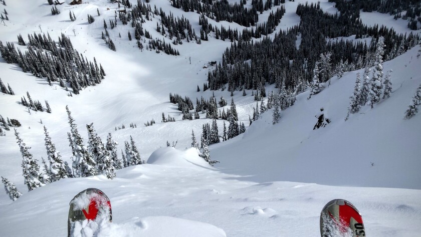 A skier prepares to drop down a steep chute on the Throne at Crystal Mountain.