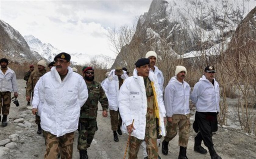 In this photo released by Inter Services Public Relations on Sunday, April 8, 2012, Pakistan's army chief Gen. Ashfaq Parvez Kayani, center, visit to avalanche incident site in Siachen, in northern Pakistan. Rescue workers used bulldozers Sunday to dig through huge banks of snow following a massive avalanche a day earlier that engulfed a military complex and buried at least 135 people, most of them soldiers, in a mountain battleground close to the Indian border. (AP Photo/Inter Services Public Relations) NO SALES
