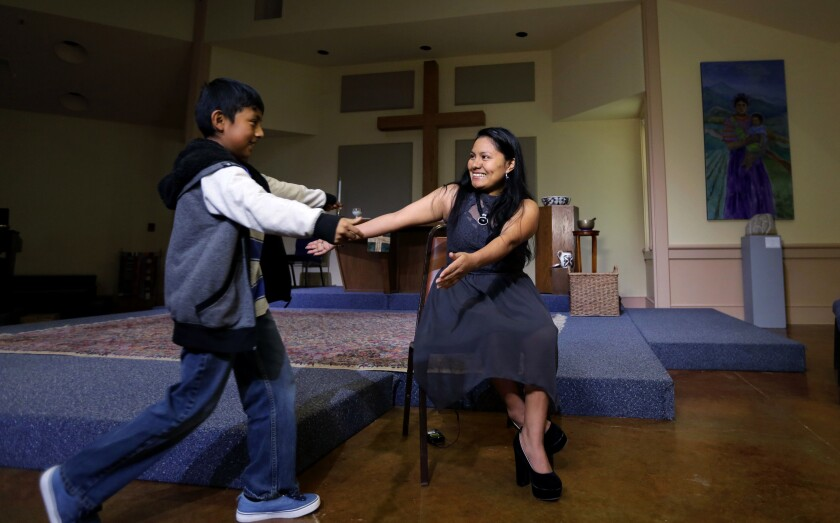 A woman and boy, inside a church, reach out their arms to each other.