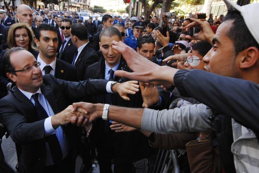 French President Francois Hollande, left, greets Algerians as he walks in Algiers on Thursday.