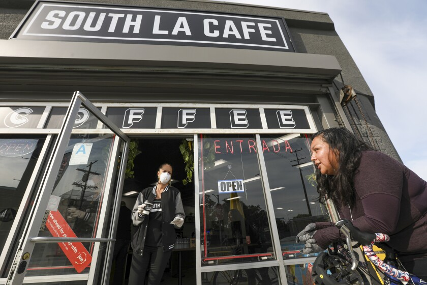 Celia Ward-Wallace, left, brings a takeout order to Sandra Flores at South LA Cafe.