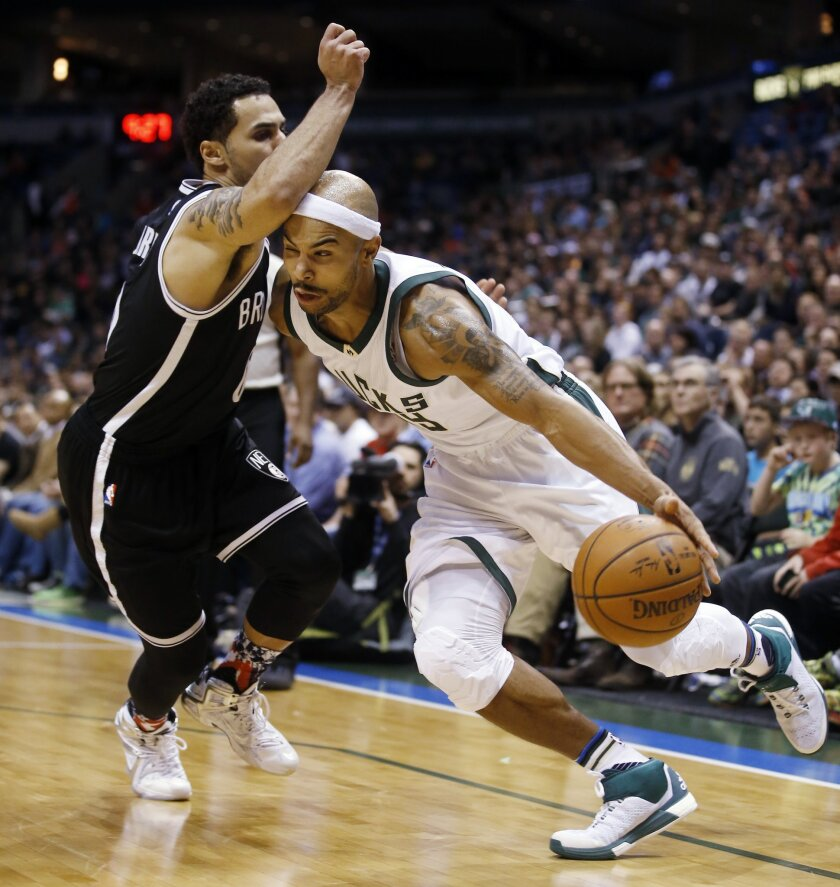 Milwaukee Bucks' Jerryd Bayless is fouled as he drives past Brooklyn Nets' Shane Larkin during the second half of an NBA basketball game Saturday, Nov. 7, 2015, in Milwaukee. The Bucks won 94-86. (AP Photo/Morry Gash)