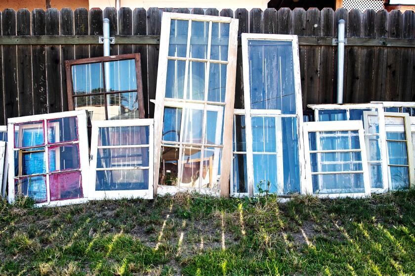 Wood-frame windows lean against a fence.