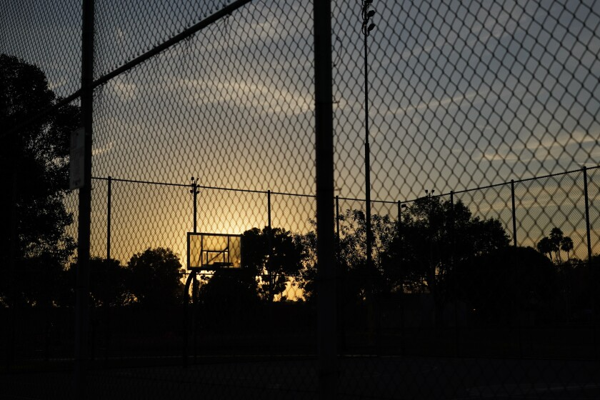 The sun sets behind a basketball backboard in a park temporarily closed due to COVID-19 in Commerce, Calif., Wednesday, Dec. 9, 2020. Thirteen counties in Northern California will be placed under the state's most restrictive coronavirus rules this week because capacity in intensive care units has fallen below 15%, and officials warned Wednesday that hospitals across the state are filling up with COVID-19 patients. (AP Photo/Jae C. Hong)