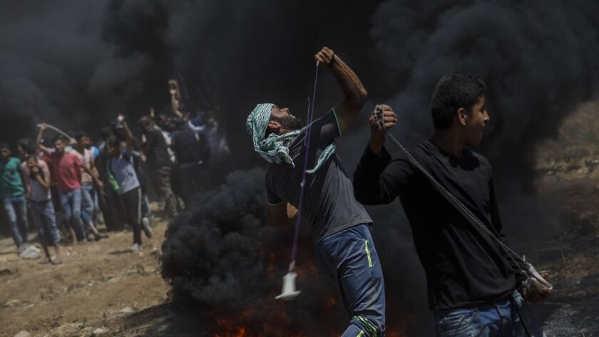 Protesters deploy projectiles toward the border fence separating Israel and the Gaza Strip.