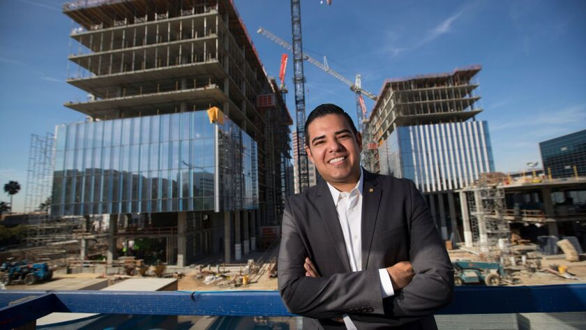 Long Beach Mayor Robert Garcia stands outside the Port of Long Beach headquarters, left, and City Hall, right, which are being developed by the city in partnership with a consortium of private companies.