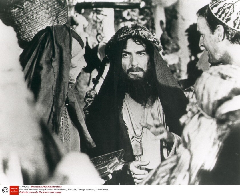 "George Harrison, center, with Monty Python members Eric Idle, left, and John Cleese in the comedy troupe's 1979 film, ""Life of Brian."""
