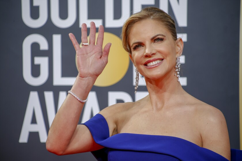 A woman in a blue off-the-shoulder dress and diamond jewelry waves.