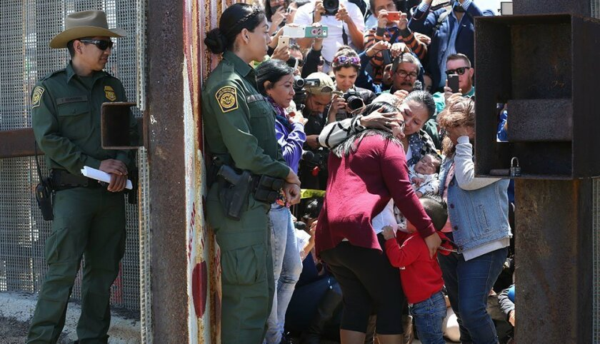 Border Patrol agents stand by at the Door of Hope as Gabriela Esparza, left, and son Leonel Martinez Esparza, fall into the arms of family members Maria del Carmen Flores, with her infant, and Susanna Carmen Esparza Flores, from the Tijuana side of the wall.