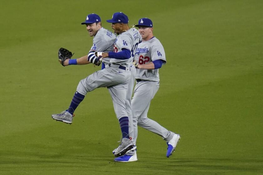 De izquierda a derecha, AJ Pollock, Mookie Betts y Luke Raley, de los Dodgers de Los Ángeles