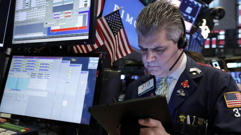 Trader John Panin works on the floor of the New York Stock Exchange.
