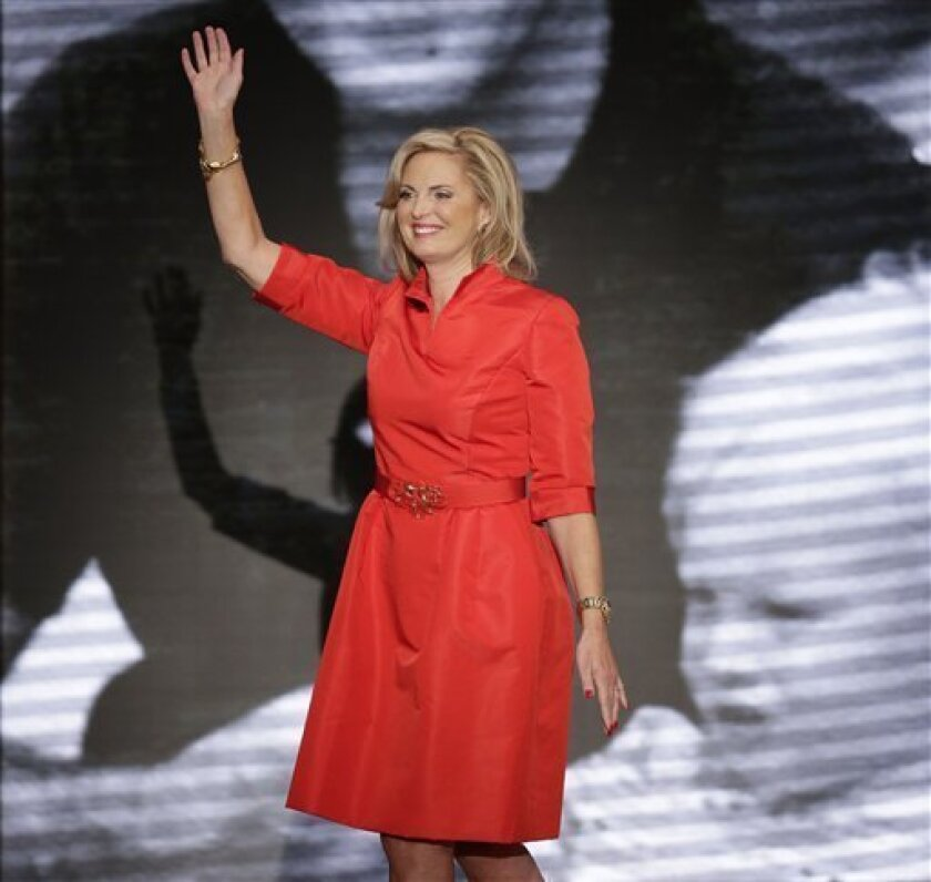 This Aug. 28, 2012 photo shows Ann Romney, wife of U.S. Republican presidential candidate Mitt Romney, waving after addressing the Republican National Convention in Tampa, Fla. Romney wore a knee-length bright red belted dress designed by Oscar de la Renta. (AP Photo/J. Scott Applewhite)