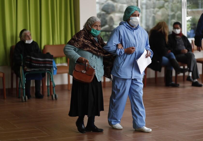 Una enfermera ayuda a una anciana a caminar para recibir su inyección de la vacuna Sinopharm COVID-19 en el hogar de ancianos San Ramón durante el inicio de la inmunización para personas mayores de 80 años en La Paz, Bolivia, el lunes 5 de abril de 2021. ( Foto AP/Juan Karita)