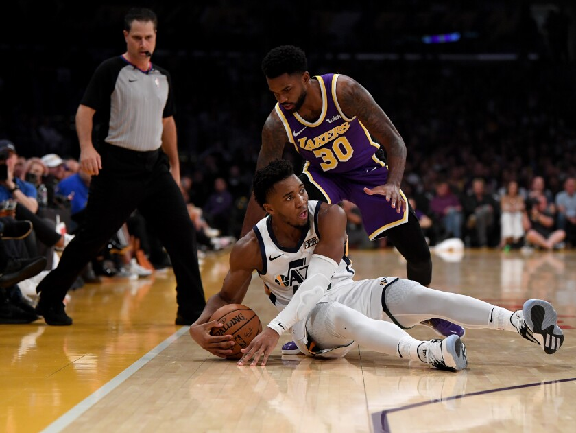 Lakers guard Troy Daniels looks to steal the ball from Jazz guard Mike Conley during their game Friday night at Staples Center.