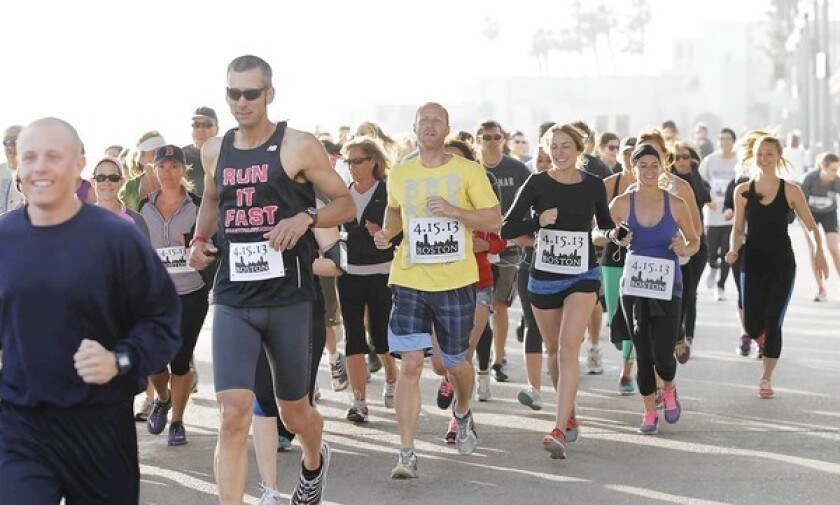 """Nearly 80 runners take off for an afternoon 4-mile run at the Huntington Beach Pier with """"Runners United to Remember"""" bibs attached to honor of those affected by the Boston Marathon bombings last week."""