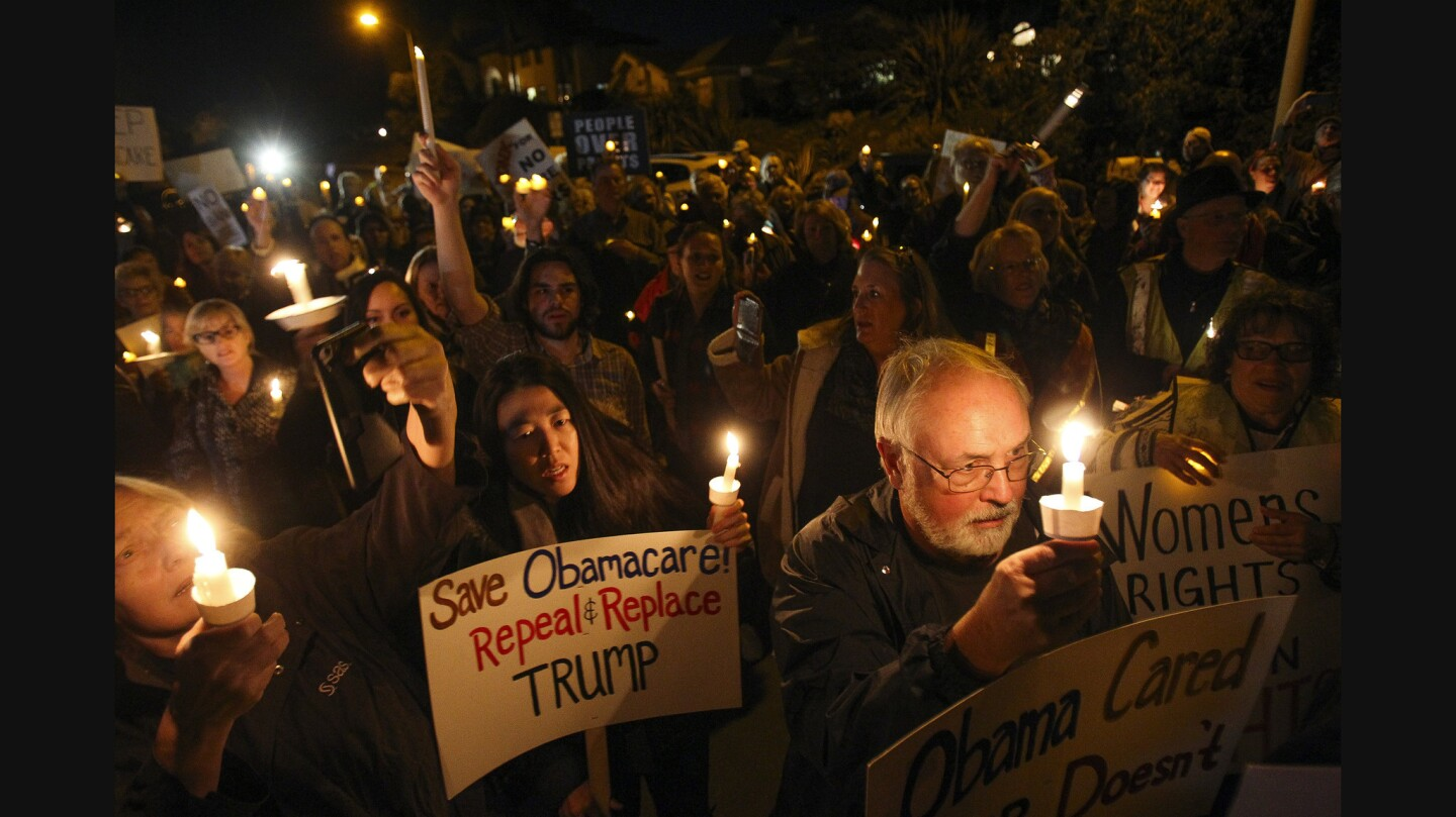 Around 200 people stand in front of the home of Republican Congressman Darrell Issa as they hold a candlelight vigil as a form of protest.