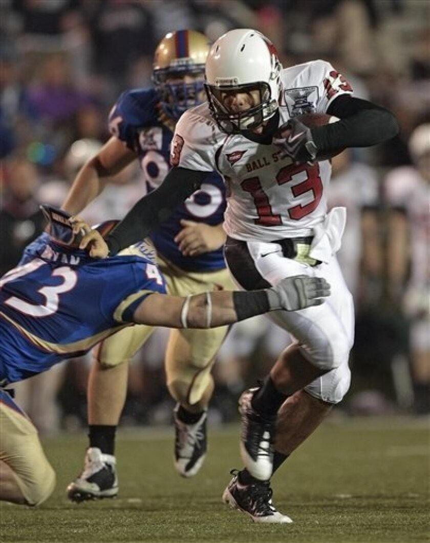 Ball State quarterback Nate Davis (13) escapes the tackle of Tulsa's Victor Pongonis (43) during the first half of the GMAC Bowl NCAA college football game at Ladd-Peebles Stadium in Mobile, Ala., Tuesday, Jan. 6, 2009.  (AP Photo/Dave Martin)