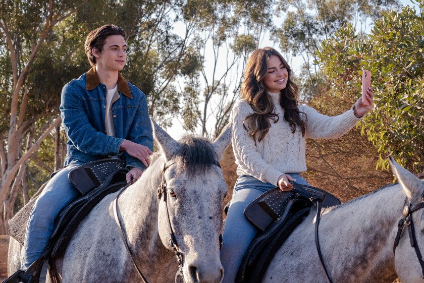 A girl takes a selfie with her male love interest while on horseback