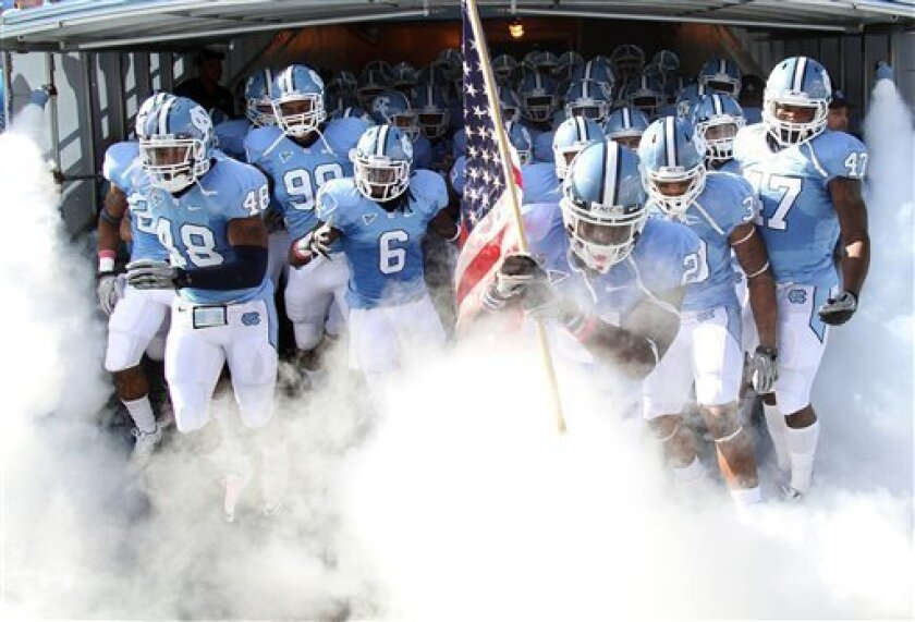 North Carolina safety Da'Norris Searcy (21) leads the team onto the field, carrying the America flag, at the start of an NCAA college football game in Chapel Hill, N.C., Saturday, Oct. 9, 2010. North Carolina won 21-16. (AP Photo/Jim R. Bounds