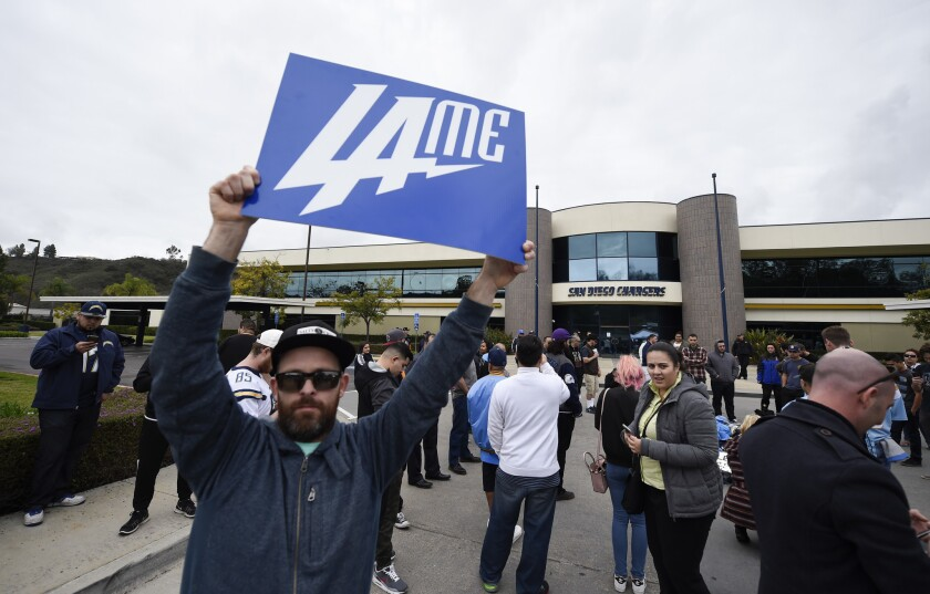 A San Diego Chargers fan holds up a sign in front of Chargers headquarters after the team announced that it will move to Los Angeles.