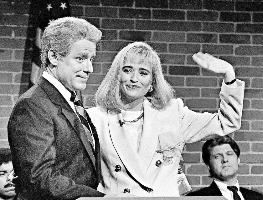 "In a ""Saturday Night Live"" skit, Phil Hartman portrays then-President Bill Clinton with Jan Hooks as Hillary Rodham Clinton."