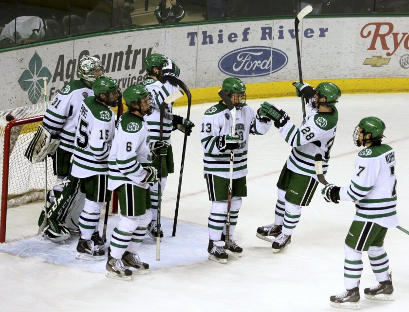 FILE - In this Jan. 10, 2014 , file photo, North Dakota hockey players celebrate a win over Colorado College in Grand Forks, N.D. UND President Mark Kennedy says the school's athletic department needs to figure out a way to save money, and that may include leaving the Big Sky Conference. The Grand