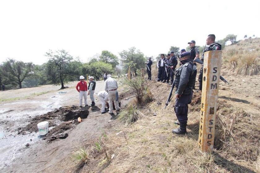 Fotografía de archivo de expertos en ductos custodiados por la Policía Federal tras una ordeña clandestina de un ducto de la empresa Petróleos Méxicanos (Pemex). EFE/Archivo