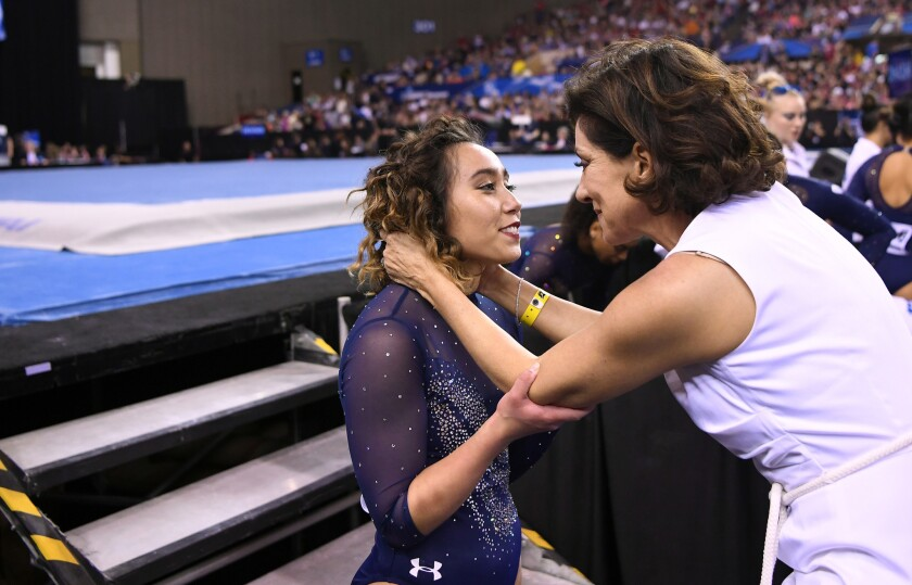Katelyn Ohashi is held by Coach Valorie Kondros Field after Ohashi's last floor routine as a senior Saturday at the NCAA gymnastics championship in Fort Worth, Texas.