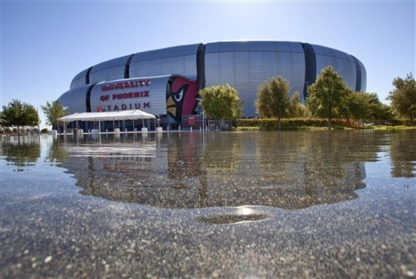 University of Phoenix Stadium is reflected in the pool at Sportsman's Park in October 2011, in Glendale, Ariz. The 2015 Super Bowl will be played in Phoenix -- the third time city has hosted the game.(AP Photo/Matt York)