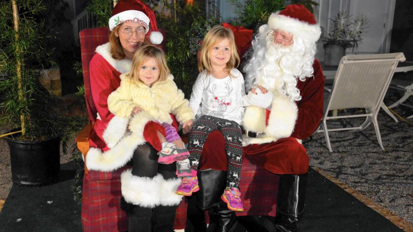Barbara and Michael Lawler portray Santa and Mrs. Claus during the Balboa Island Christmas celebration Dec. 4 as they greet sisters Sunflower and Bristol Trump. The Lawlers' outfits were stolen from their car Tuesday night.