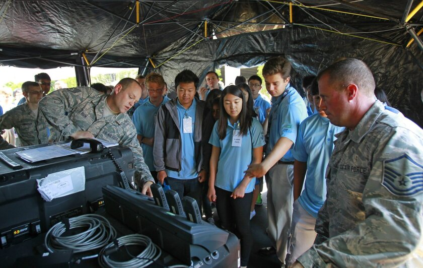 Air National Guard Staff Sgt. Alex Bivin, left, and Master Sgt. Daryl Kinney, right, do a communication satellite field demonstration for students in a San Diego Cyber Security Boot Camp at National University.  The two are from the 147th Combat Communication Squadron at the San Diego Air National