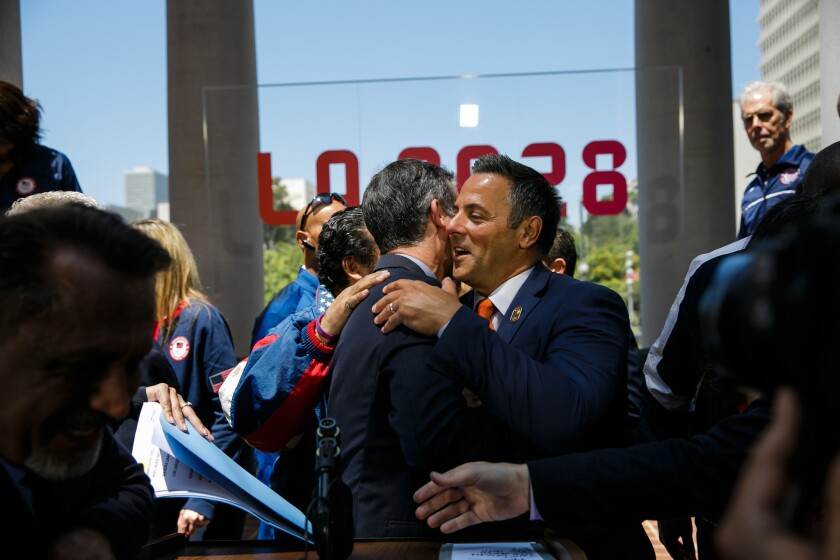 Mayor Eric Garcetti is congratulated by council member Joe Buscaino at a news conference to announce the vote city's approval of a deal to host the 2028 Olympics.