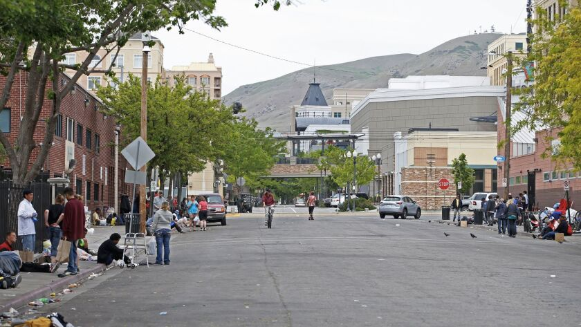 People linger outside Salt Lake City's Road Home shelter on Rio Grande Street in view of the Gateway, a high-end retail shopping center.