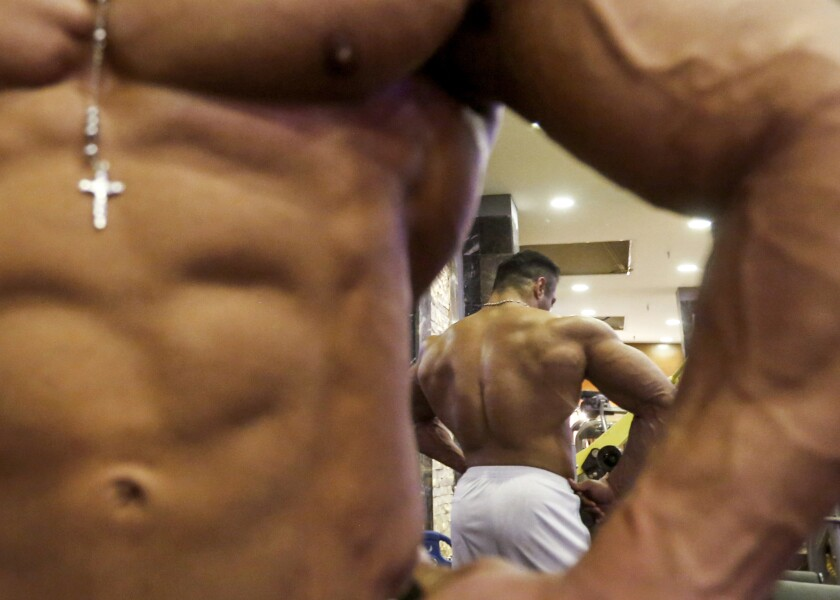 Close-up of a bodybuilder, also seen reflected from behind.