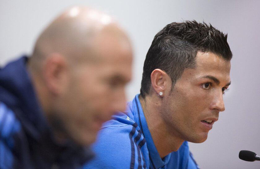 Real Madrid's Cristiano Ronaldo listens to a question during a press conference at the Olympic Stadium in Rome, Italy, Tuesday, Feb. 16, 2016. Real Madrid faces Roma in a UEFA Champions League soccer match Wednesday. In foreground is Real Madrid coach  Zinedine Zidane.  (Claudio Peri/ANSA via AP Ph