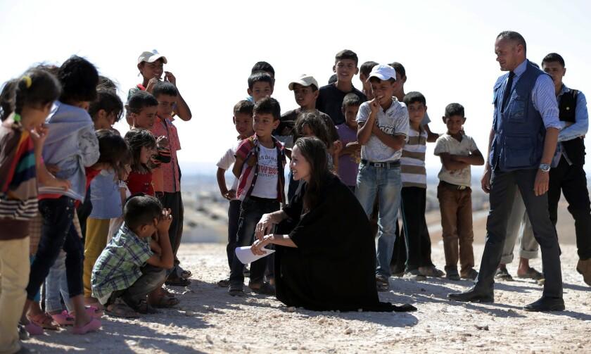 La actriz y enviada especial de la agencia de la ONU para los refugiados Angelina Jolie charla con niños durante una visita a un campo para refugiados sirios en Azraq en el norte de Jordania el viernes 9 de septiembre de 2016. Jolie pidió un mayor apoyo para los refugiados. (Foto AP/Ahmad Alameen)