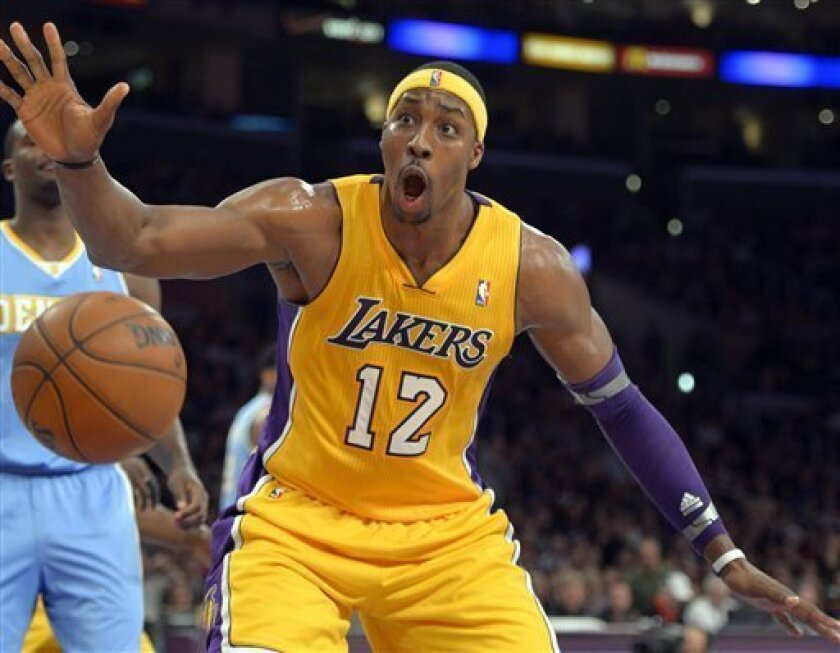 Los Angeles Lakers center Dwight Howard reacts after dunking during the first half of their NBA basketball game against the Denver Nuggets, Friday, Nov. 30, 2012, in Los Angeles. (AP Photo/Mark J. Terrill)